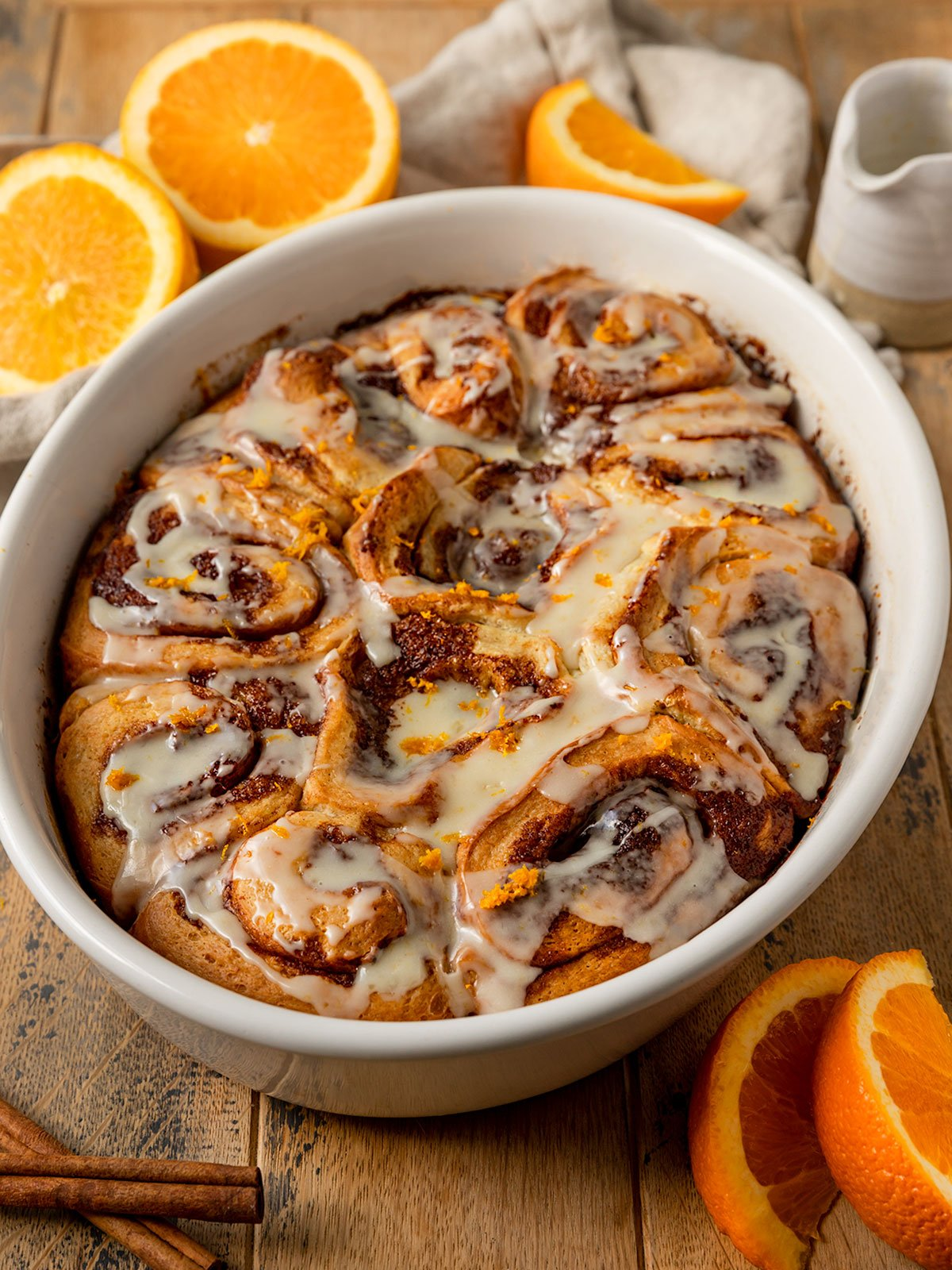 oval baking tray filled with orange cinnamon rolls