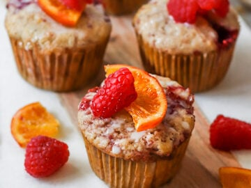a board of raspberry jam muffins topped with candied oranges and fresh raspberries