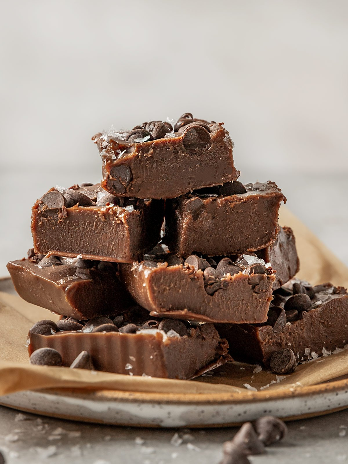 stack of chocolate fudge with chocolate chips and flaky salt on a plate