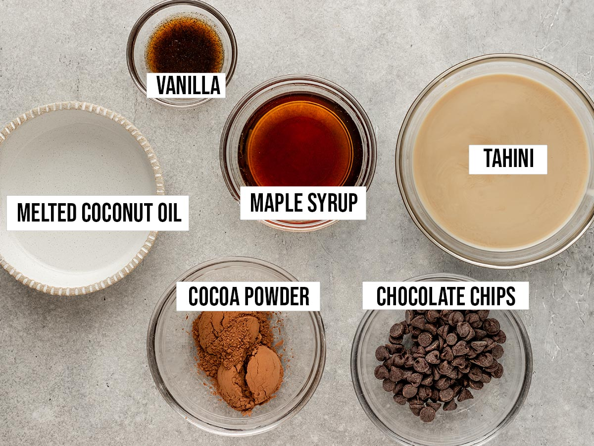 ingredients in bowls including tahini, coconut oil, maple syrup, vanilla, cocoa powder, and chocolate chips