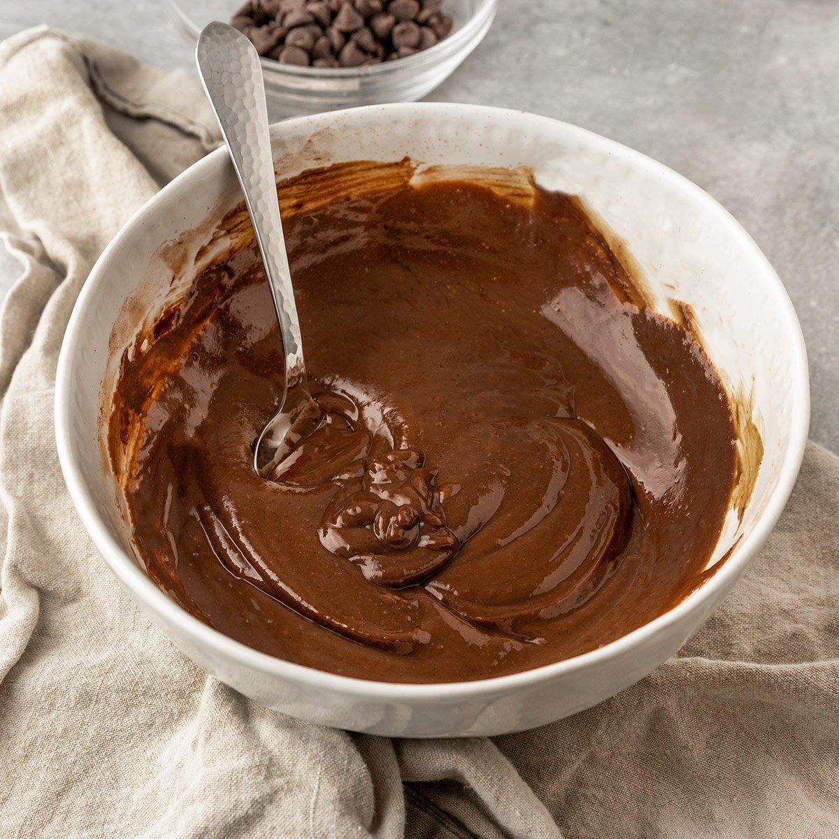 bowl of chocolate tahini fudge  batter with a spoon