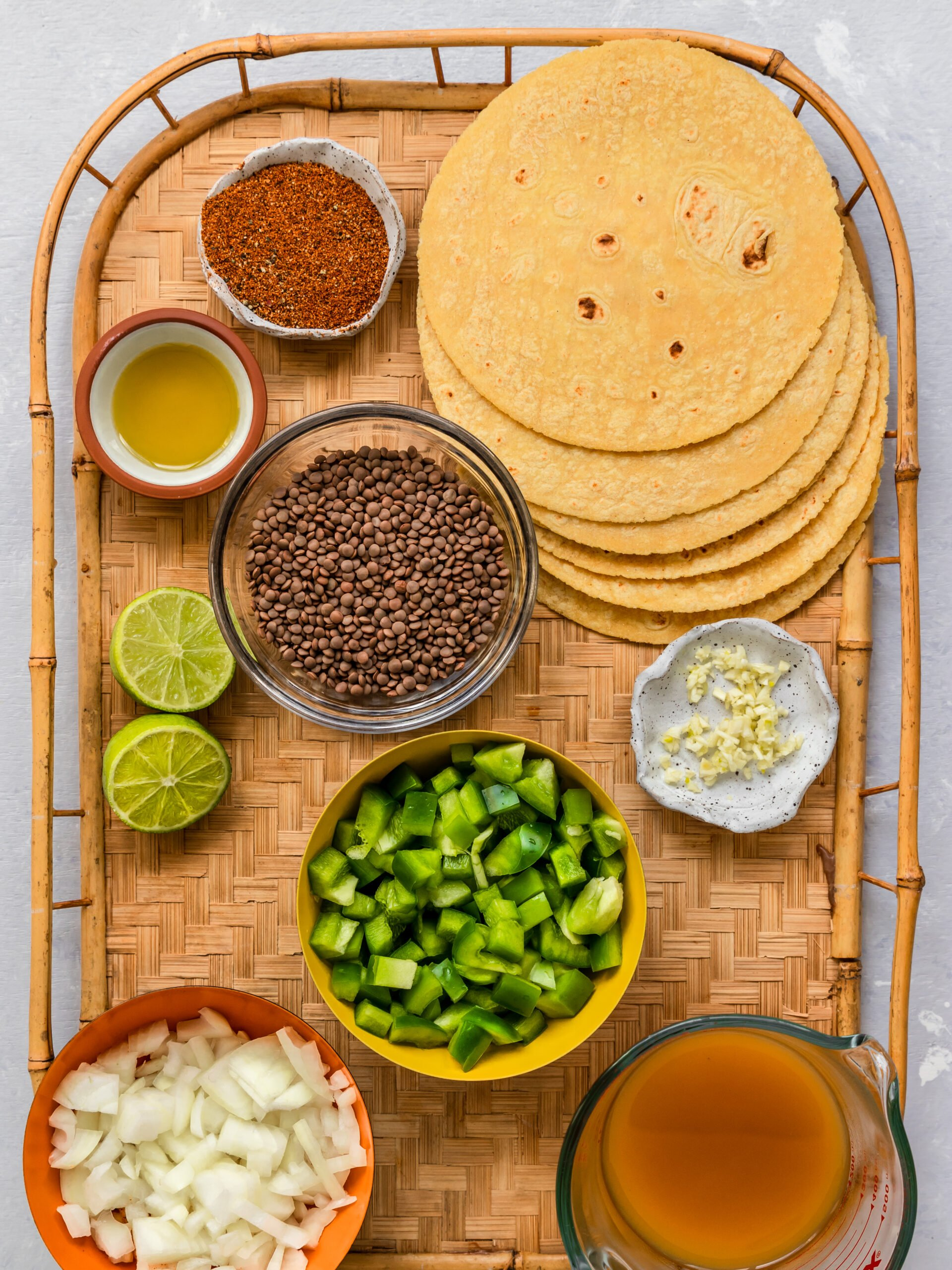 flour tortillas, lentils, oil, taco seasoning, peppers, onions, garlic, veggie broth, and lime juice on tray