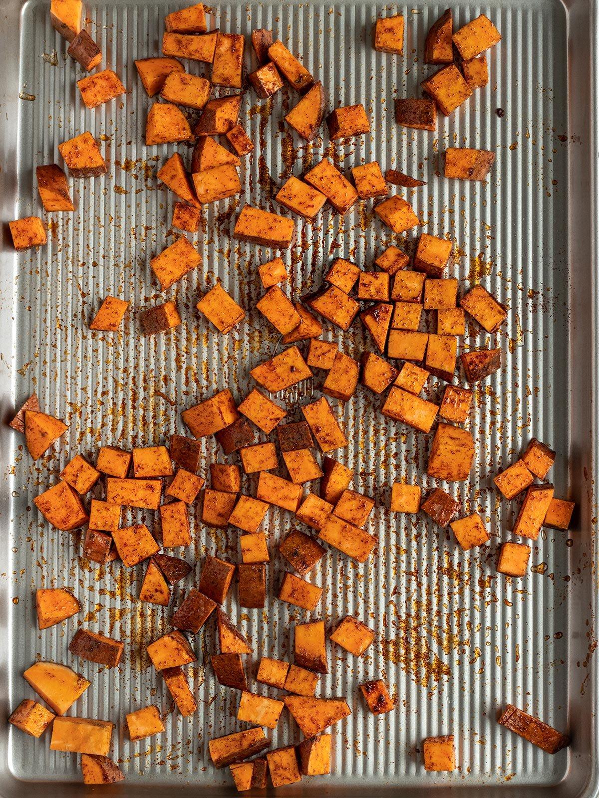 seasoned sweet potatoes on a baking tray before roasting