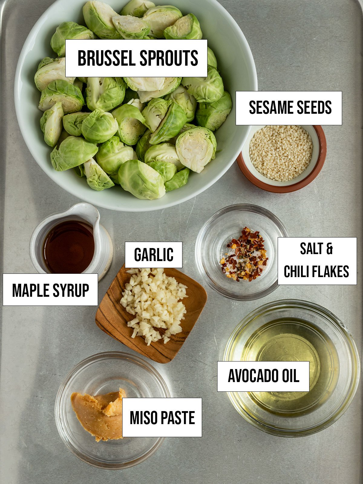 ingredients including brussel sprouts, maple syrup, miso paste, avocado oil, garlic, salt, chili flakes, sesame seeds