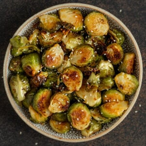 bowl of roasted brussel sprouts with miso glaze and sesame seeds