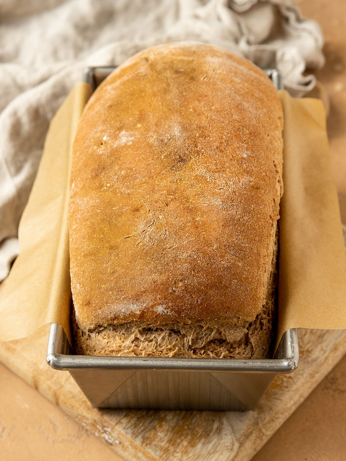 baked loaf of spelt bread in a parchment lined pan