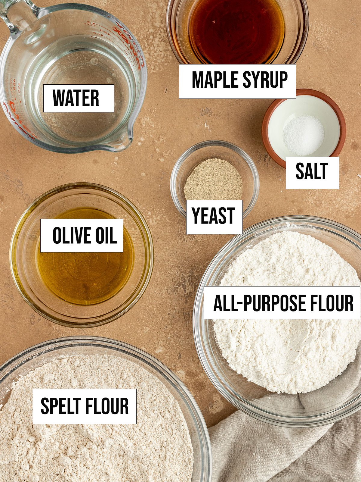 ingredients including spelt flour, all-purpose flour, maple syrup, olive oil, water, yeast, and salt