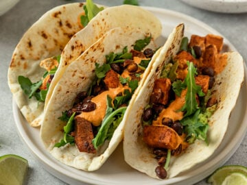 three sweet potato black bean tacos on a plate with arugula and an orange chipotle sauce on top