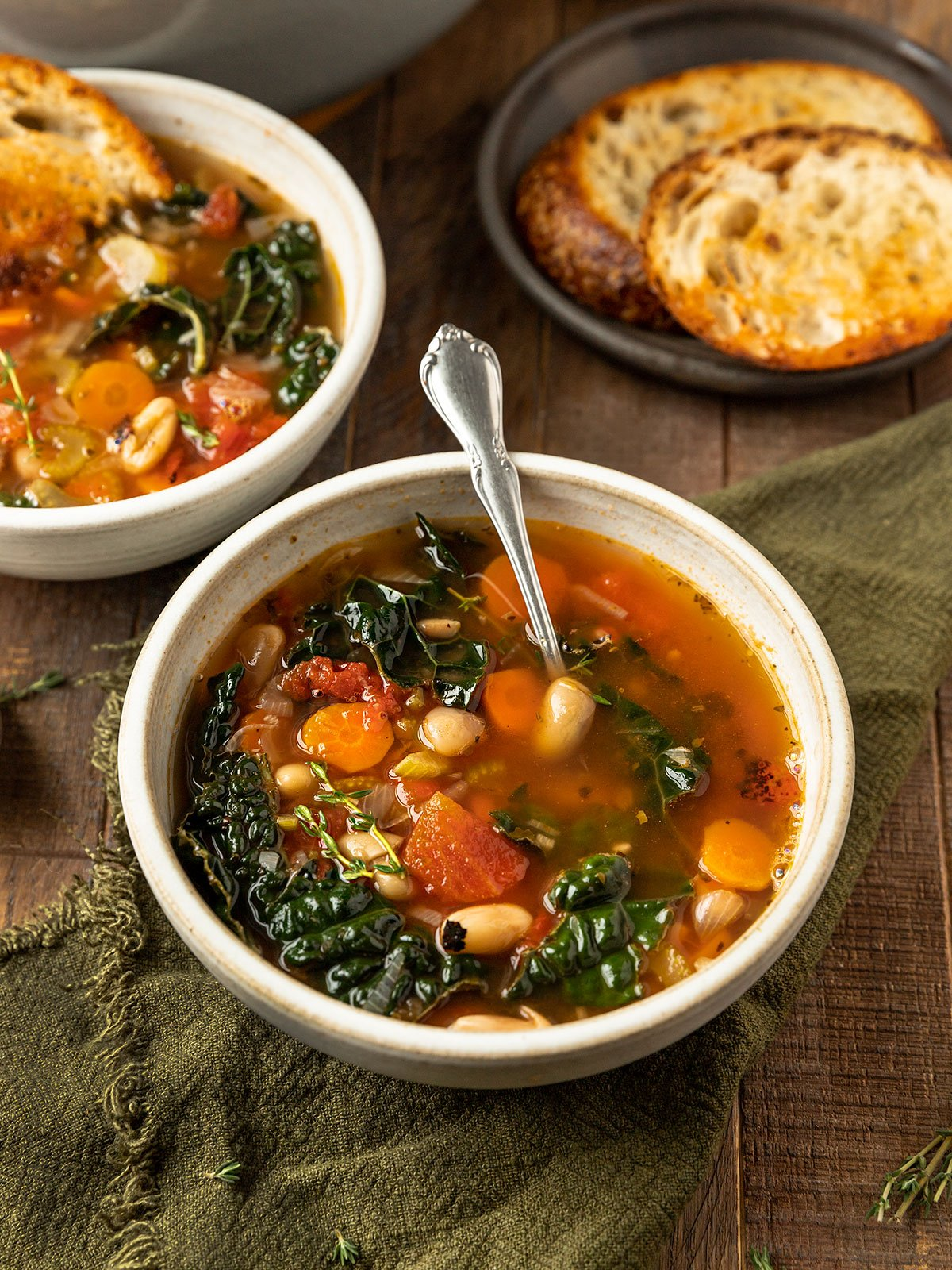 bowl of tuscan vegetable white bean soup with spoon and side of bread