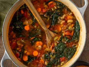 cast iron pot full of vegetable soup with white beans and kale
