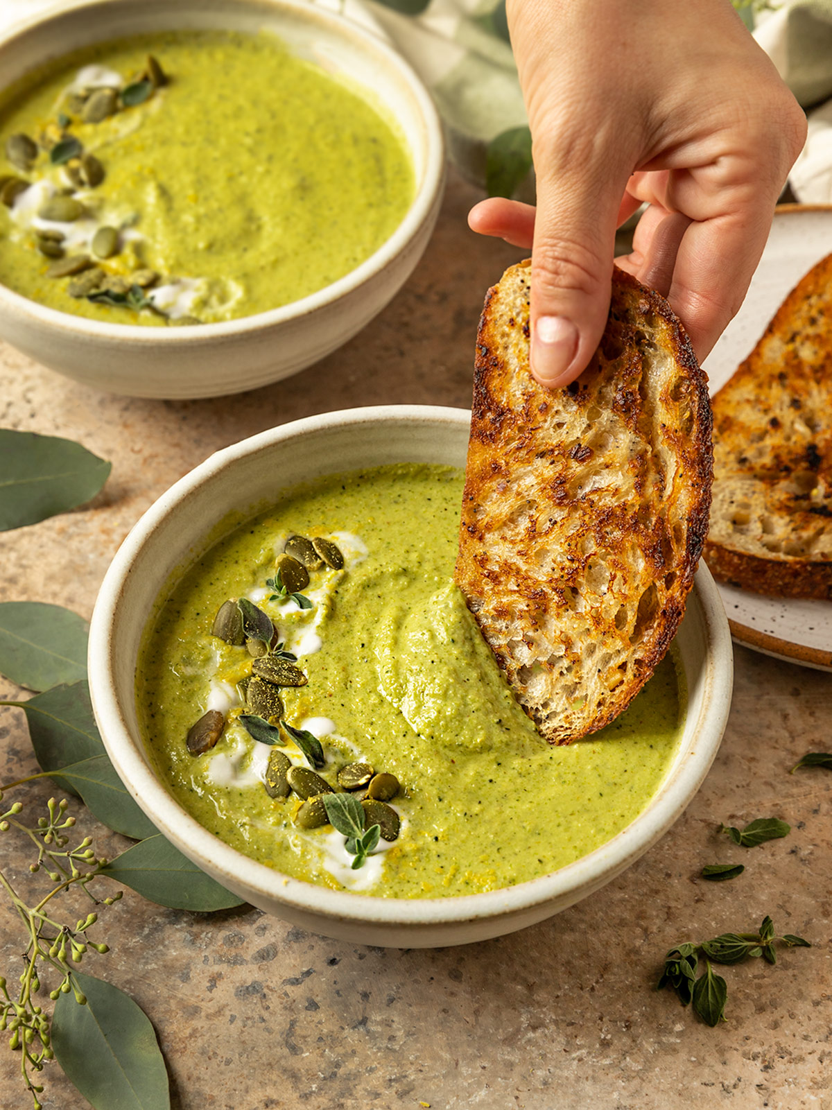 hand dipping toasted bread into a bowl of broccoli soup