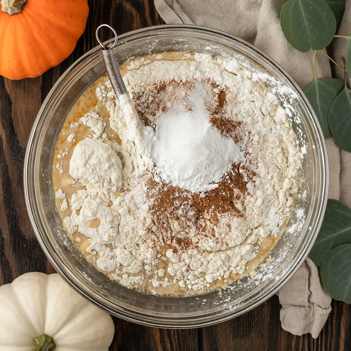 dry ingredients getting added to bowl to make pumpkin pancake batter