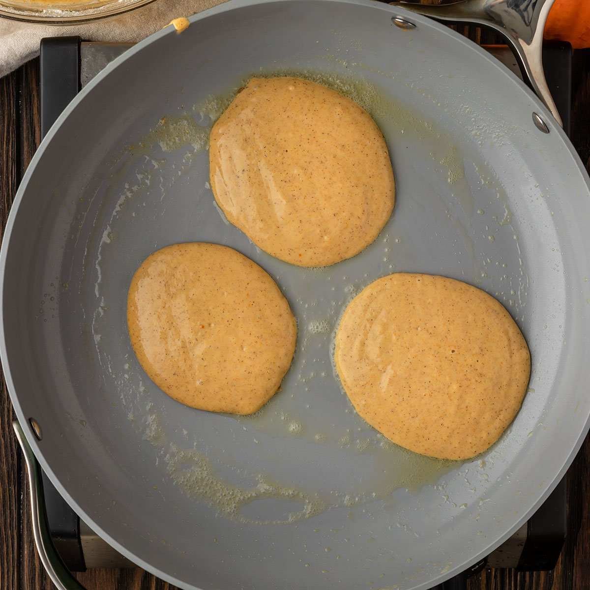three pumpkin pancakes being cooked on a pan