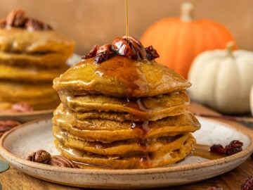 maple syrup being poured onto pumpkin pancakes topped with pecans and dried cranberries