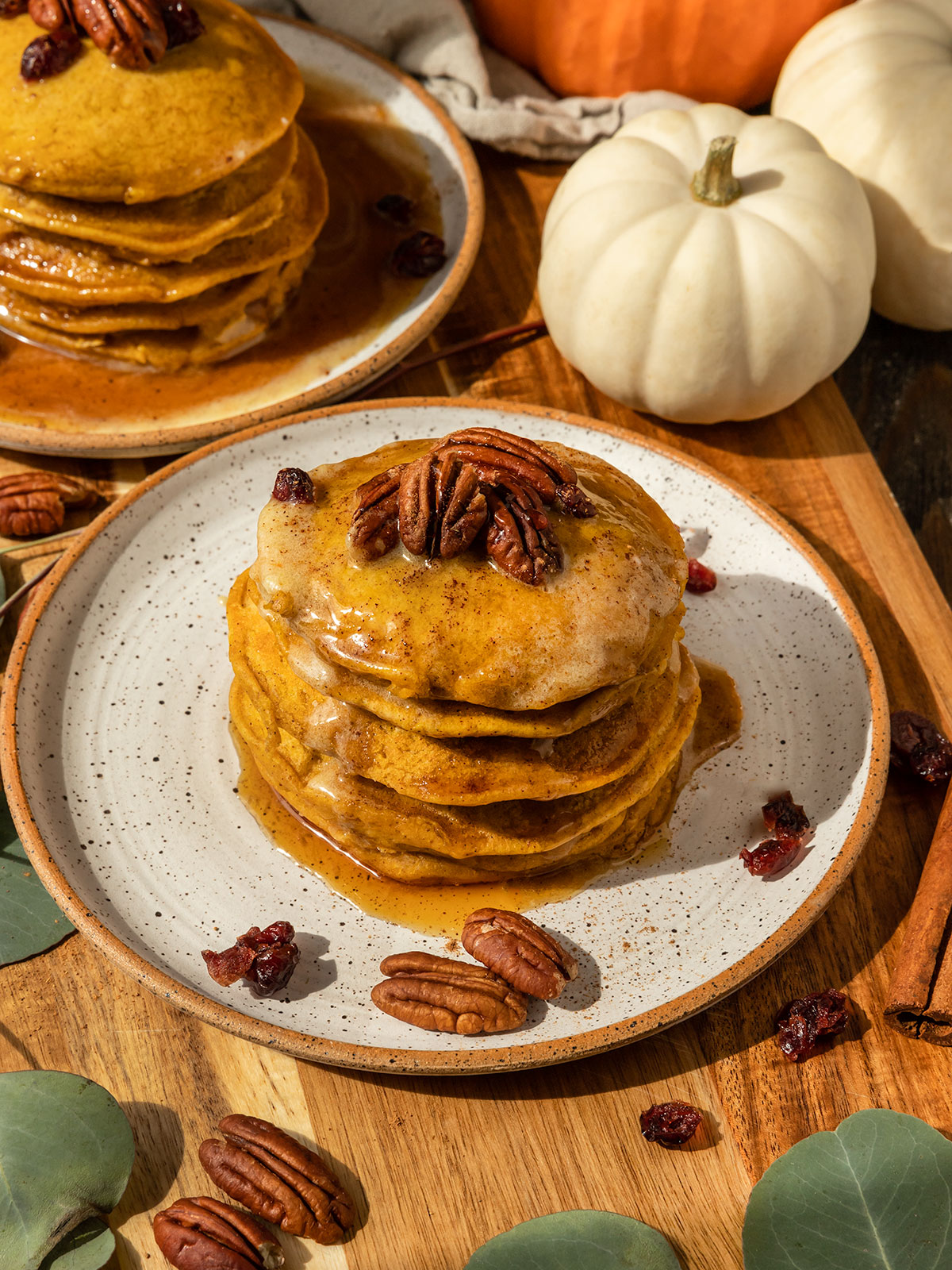 stack of pumpkin pancakes topped with maple syrup, pecans, and dried cranberries