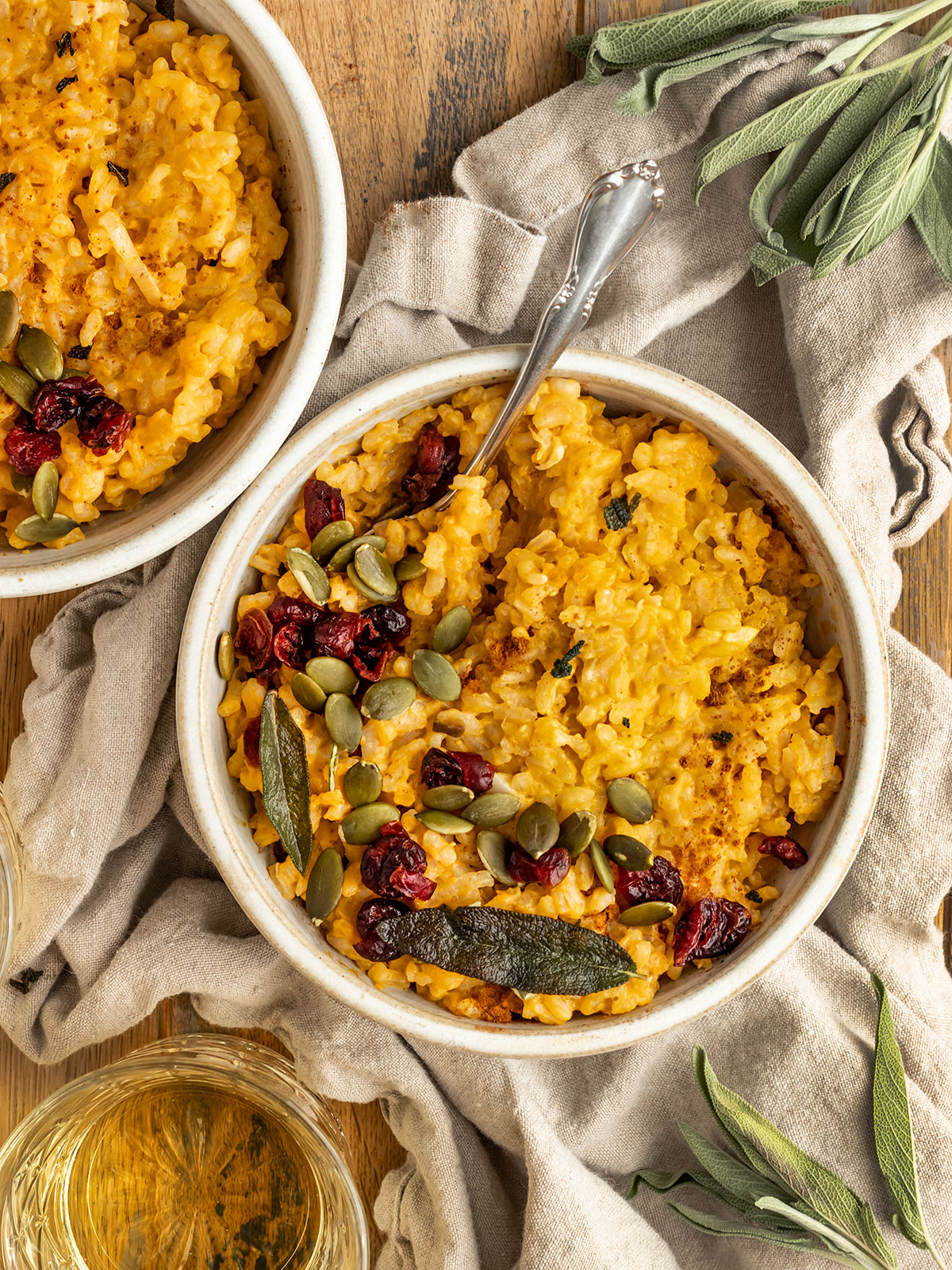 two bowls of pumpkin risotto with pumpkin seeds, fried sage, and dried cranberries