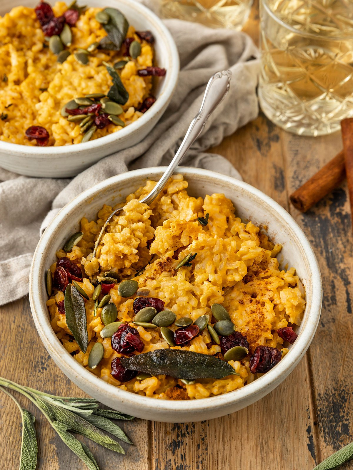 a bowl of pumpkin risotto with pepitas, fried sage, and dried cranberries
