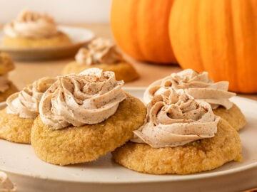 two frosted pumpkin sugar cookies on plate with pumpkins behind them