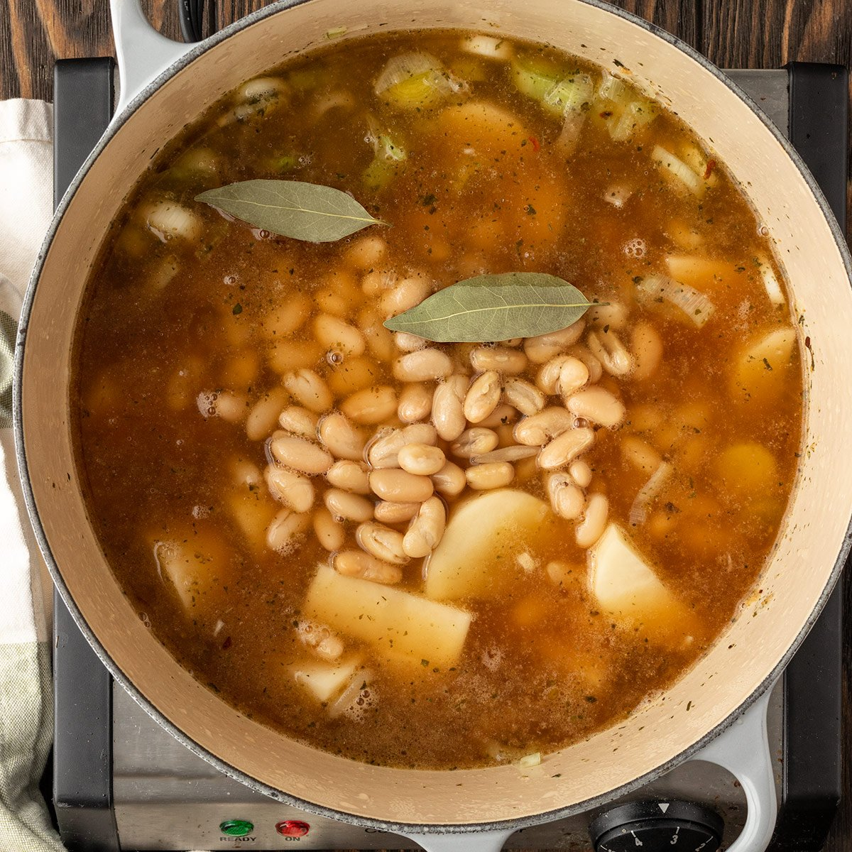 beans, broth, potatoes, and bay leaves being added to soup