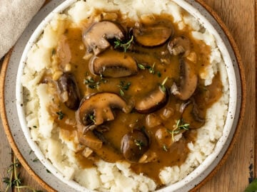 bowl of mushroom gravy with fresh thyme on top of mashed potatoes