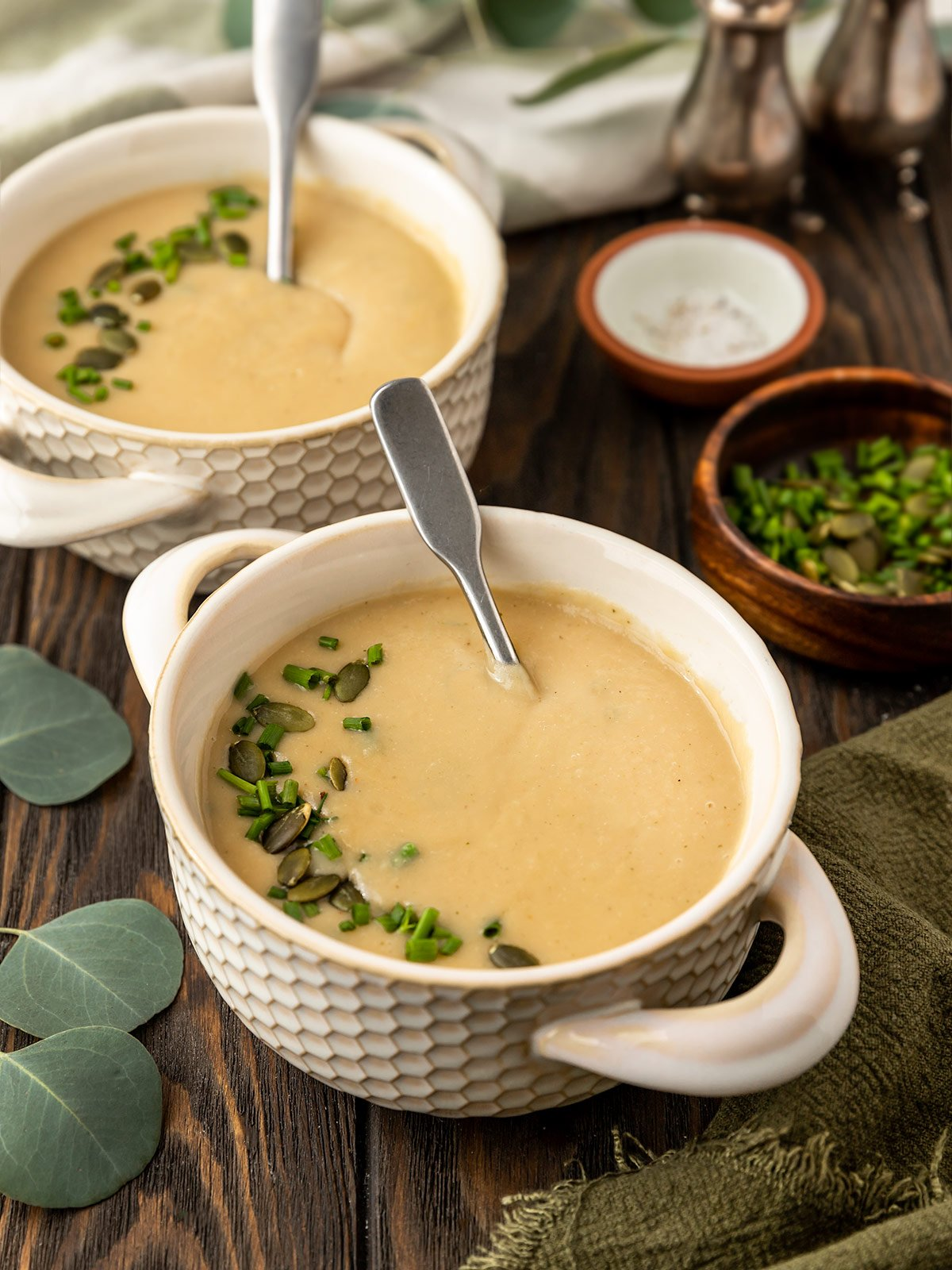 two bowls of potato leek soup with pepitas and chives on top